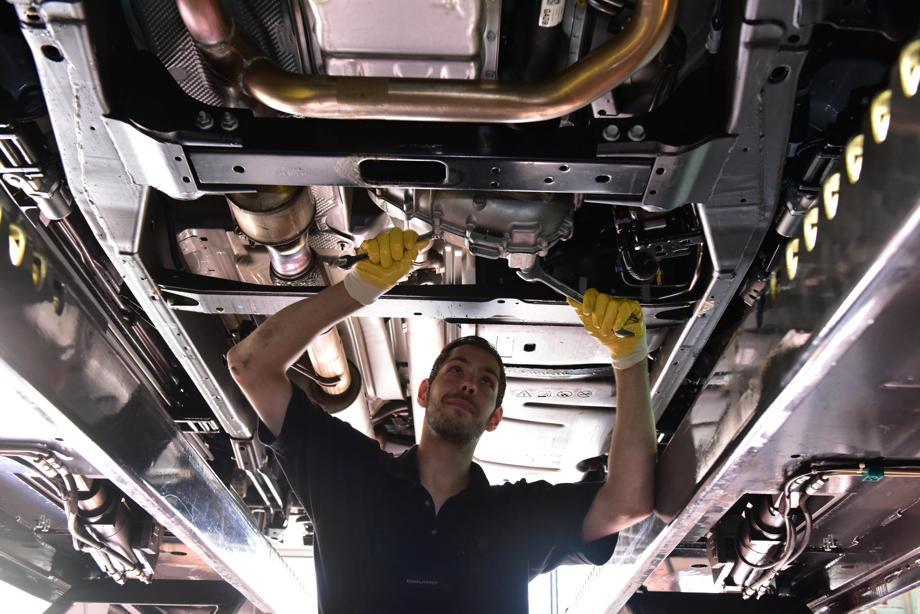 Mitarbeiter unter Fahrzeug in Werkstatt